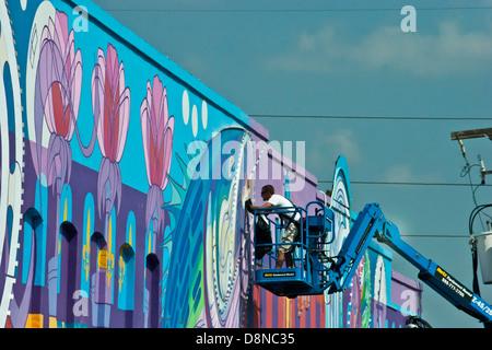 Man painting wall art downtown Shreveport, Louisiana USA - Stock Image