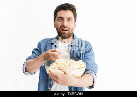 Portrait of an excited handsome bearded man wearing casual clothes standing isolated over white background, watching a movie, eating popcorn - Stock Image
