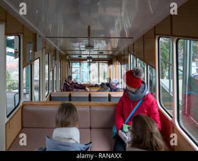 Dresden, Germany, December 15., 2018: Inside the wagon of the oldest suspension railway in the world with passengers in the front area of the wagon. - Stock Image