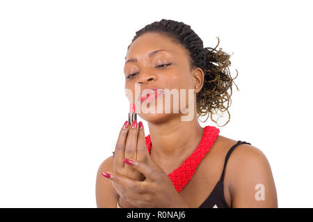 Closeup of beautiful African woman looking at her lipstick held with her fingertips. - Stock Image