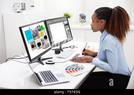 Young Female Designer Editing Photos On Computer In Office - Stock Image