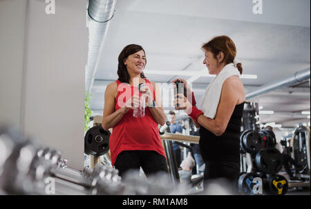 Two senior women in gym resting after doing exercise, holding water bottles. - Stock Image