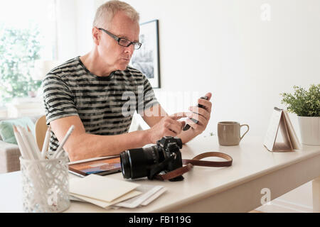 Man in home office using smartphone - Stock Image