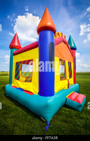 Bounce house inflatable jumpy castle in a large open yard. - Stock Image