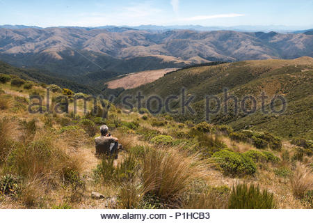 Man sits on hill slope, mt.Thomas Conservation Area, Canterbury, New Zealand - Stock Image