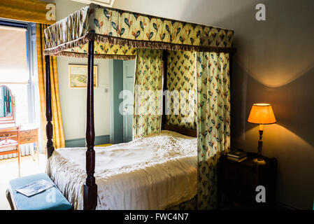 Four-poster bed with curtains in an old fashioned bedroom - Stock Image