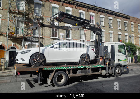 car being towed away on a flat bed truck by local council enforcement team in London England UK - Stock Image