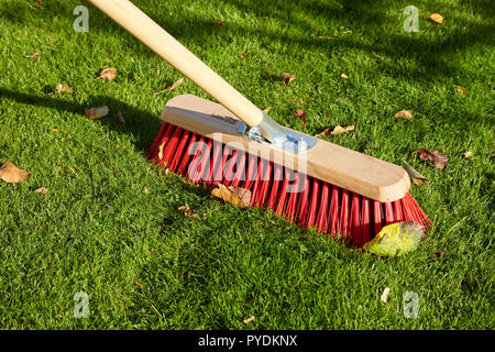 Red Brush Sweeping Leaves off Grass Autum UK - Stock Image