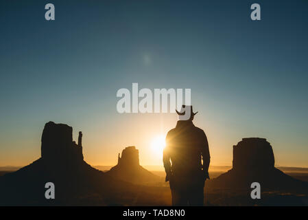 USA, Utah, Monument Valley, silhouette of man with cowboy hat  watching sunrise - Stock Image