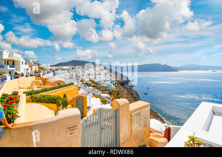 A scenic view of the Santorini caldera and the Aegean Sea from a resort terrace as tourists walk the main street in the hillside village of Oia, Greec - Stock Image