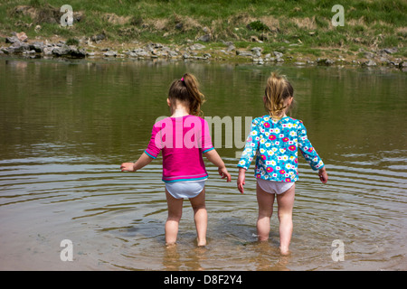 2 sisters aged 3 and 4 years old, playing in the water at the beach. - Stock Image