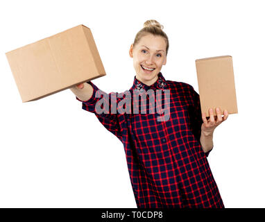 woman holding blank cardboard boxes in hands isolated on white background - Stock Image