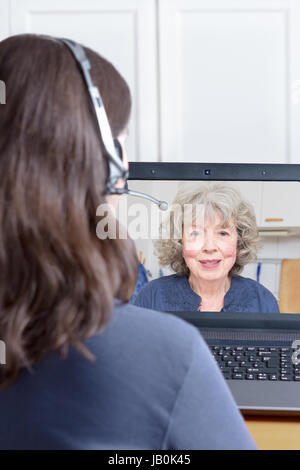 Woman with headset at her desk in front of her laptop making a video call with her grandmother, copy or text space - Stock Image
