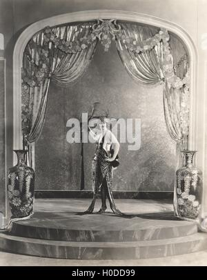Showgirl posing under archway - Stock Image