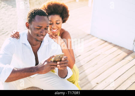 Beautiful afro american couple use modern phone to message or call friends away -  Relationship and friendship concept for alternative people - sunny  - Stock Image