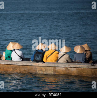 Tourists wearing tradtional hats in a boat in Miyajima, Japan - Stock Image