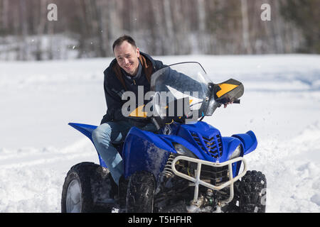 A winter forest. Cold weather. A man in warm jacket riding a big snowmobile - Stock Image