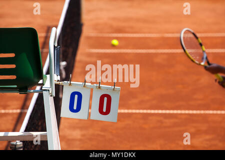 Tennis player umpire chair with scoreboard and racket on a clay court in the beginning of the game. - Stock Image