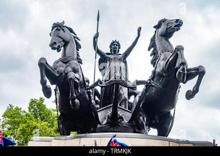 A low angle view of a bronze statue of Boudica riding a chariot pulled by two horses seen from a low angle against a grey cloudy sky. - Stock Image