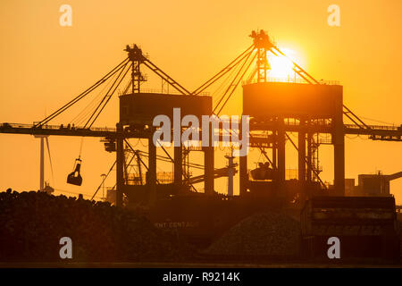 Silhouetted cranes unloading coal at sunset by the Tata steel works in Ijmuiden, North Holland, Netherlands - Stock Image