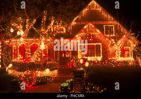 Brightly decorated home in Southern California at night during Christmas season - Stock Image
