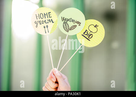 Holding stickers with healthy food slogans on the green background - Stock Image