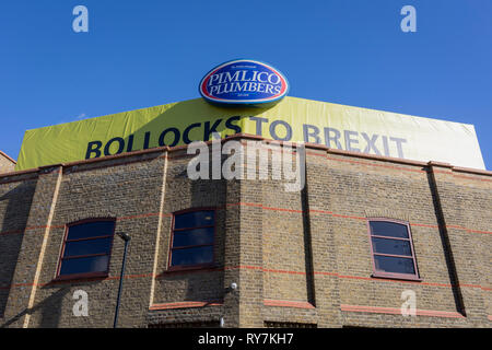 """A large banner proclaiming Bollocks To Brexit above the south London headquarters of Pimlico Plumbers, on 10th March 2019, in London, England. The controversial boss of Pimlico Plumbers is refusing to take down a giant """"bollocks to Brexit"""" sign on the roof of his HQ, despite the local council ordering him to remove it or face prosecution. Boss Charlie Mullins is refusing to take down the giant sign on the roof of his company HQ, despite the local council ordering him to remove it or face prosecution. - Stock Image"""