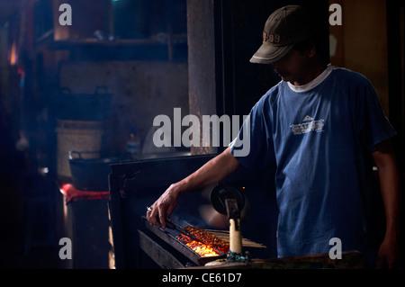 Balinese man cooking chicken satys at Ubud Markets Bali Indonesia - Stock Image