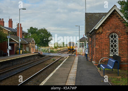 A local passenger train approaching the rural railway station of Swinderby in Lincolnshire - Stock Image