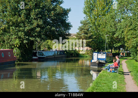 Father and son fishing by the side of the Grand Union canal on a sunny Summer day; Cosgrove, Northamptonshire, UK - Stock Image