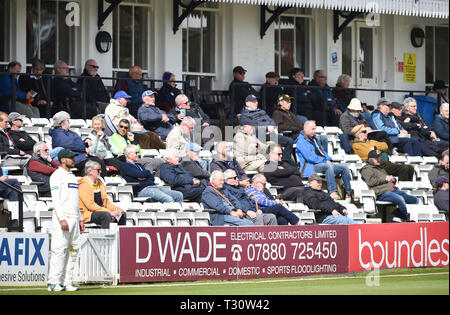 Hove Sussex, UK. 05th Apr, 2019. Specatators watch Sussex v Leicestershire in the Specasavers County Championship Division Two match at the 1st Central County Ground in Hove on a sunny but cool first morning of the season Credit: Simon Dack/Alamy Live News - Stock Image