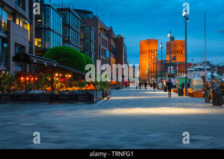 Oslo harbor, view at night of the harbor district (Aker Brygge) in central Oslo with the Town Hall building (Radhus) in the distance, Norway. - Stock Image