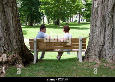 A man and a woman sit together on a park bench surrounded by huge trees, looking at one another and smiling - Stock Image