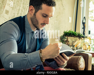 Handsome young man reading book at home - Stock Image