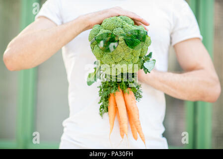 Holding broccoli with carrot like a vegetable person, healthy eating concept - Stock Image