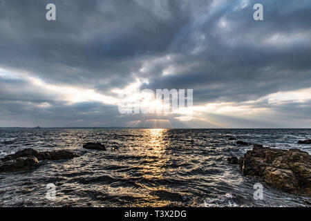 Mousehole, Cornwall, UK. 12th Apr, 2019. UK Weather. The sun made brief appearance though the clouds this morning, bringing some spectular crespicular rays over the sea at Mounts Bay Credit: Simon Maycock/Alamy Live News - Stock Image