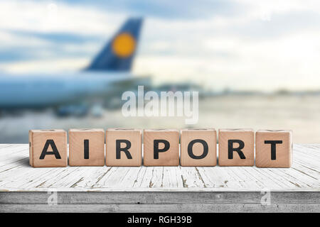 Airport word sign on a wooden surface with a plane in the background - Stock Image