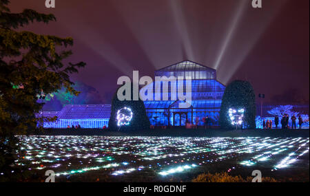 Visitors enjoying the lights in front of, inside and behind the Main Range of Glasshouses at the GlasGLOW event, where the Botanic Gardens are lit up  - Stock Image