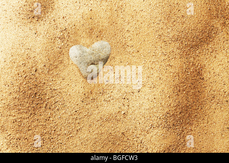 Heart Shaped Stone in Sand - Stock Image