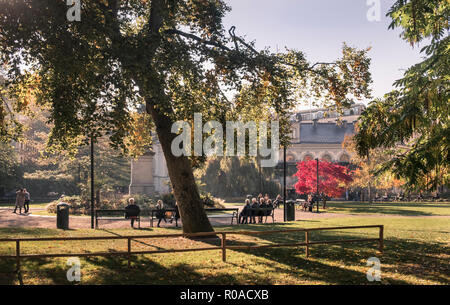 Berzelii Park, Norrmalm, Stockholm, Sweden. People enjoying autumn sunshine in a small urban park with trees and benches. - Stock Image
