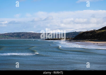Benllech, Isle of Anglesey, North Wales, UK. 10th Mar 2019. Waves roll on to Benllech beach in sunshine on a cold windy day with snow on distant mountains of Snowdonia. The weekend has seen changeable cold windy weather across the island. A snowstorm followed shortly after. Credit: Realimage/Alamy Live News - Stock Image
