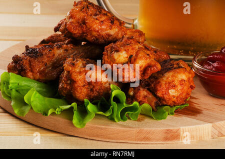 Crispy chicken wings in breadcrumbs with sause and beer on a cutting board - Stock Image