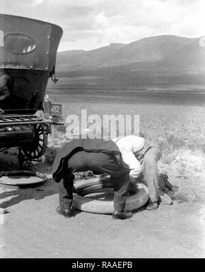 Two men change a tire on their automobile along a Colorado road, ca. 1919. - Stock Image