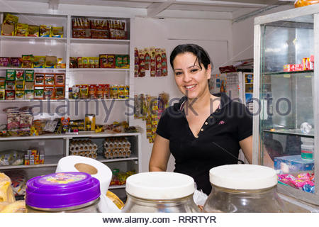 A Nicaraguan woman at her store's counter after a store renovation and expansion. - Stock Image