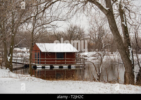 A covered floating fishing dock on a pond after a snow in Sedgwick county park, Wichita, Kansas, USA. - Stock Image