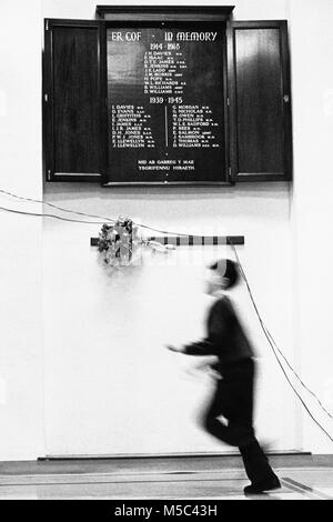 Young boy running past war memorial at small eisteddfod in village hall at Llandudoch St Dogmaels Dyfed West Wales - Stock Image