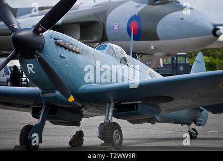 The iconic WWII British fighter plane Spitfire on the ground with an Avro Vulcan bomber in the background. - Stock Image