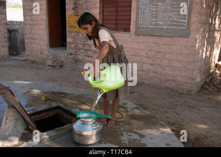 A young Bishnoi schoolgirl draws water from her village school well before lessons begin. - Stock Image