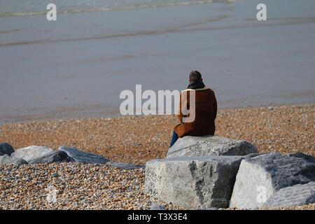 Hastings, East Sussex, UK. 12 Apr, 2019. UK Weather: Bright with sunny intervals in the seaside town of Hastings in East Sussex. A man sitting on a rock groyne wearing a brown jacket looking out to sea. © Paul Lawrenson 2019, Photo Credit: Paul Lawrenson/Alamy Live News - Stock Image