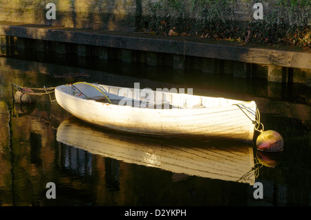 White wooden rowing boat on the River Dart at Totnes in the early morning light - Stock Image